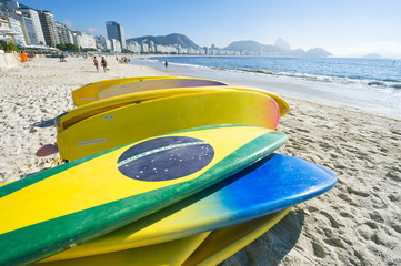 Brazilian flag stand up paddle surfboards stacked on the beach at Copacabana, Rio de Janeiro Brazil