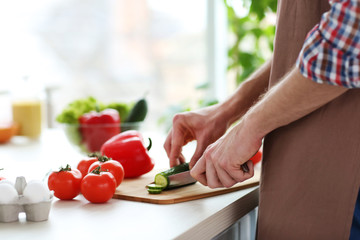 Man chopping vegetables in kitchen