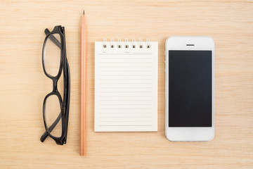 Glasses, pencil, notebook, and mobile phone on wooden background