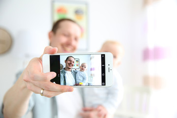 Happy young father taking a selfie with his baby, close up