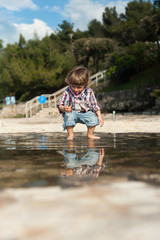 Cute little boy on the beach having fun playing and jumping in a puddle of seawater. Reflection in a puddle.