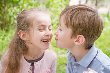 Boy trying kissing cheerful girl outdoor