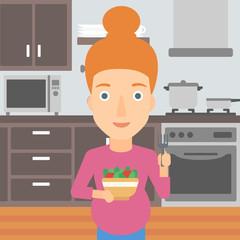 Pregnant woman eating salad.