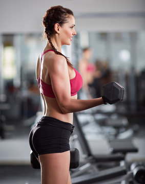 Woman doing biceps curl with dumbbells