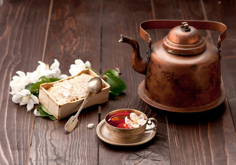 Tea with honey and white spring flowers on a wooden table