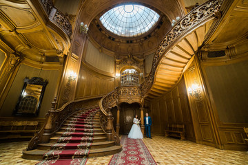 Elegant wedding couple standing at old vintage house and palace with big wooden stairs