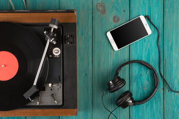 Vintage turntable, smartphone and headphones