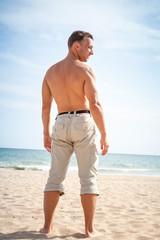 Barefoot man stands on sandy summer beach