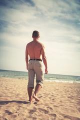 Barefoot sporty man goes on sandy summer beach