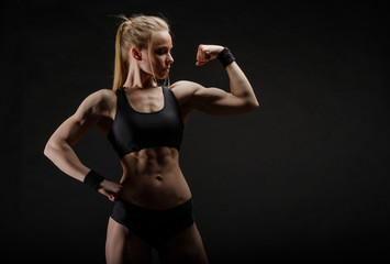 Young muscular woman posing on black