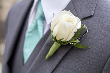 male jacket with blue tie and white rose boutonniere
