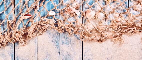 Sand, Fishing Net and Seashells on Blue Wood