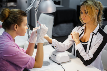 Manicure care procedure, Close-up photo Of Beautician Hand Painting Nails Of Woman In Salon