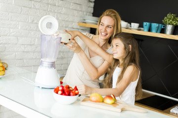 Mother and daughter blending smoothie