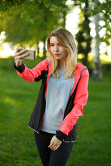 Attractive female athlete is making selfie in green park on sunny summer day. She is standing and smiling. The woman is giving thumb up and looking at the mobile phone happily