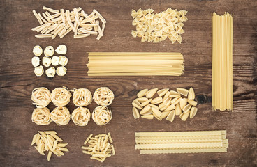 Different types of Italian uncooked pasta on rustic wooden table background, top view.
