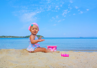 Little adorable girl playing on the beach