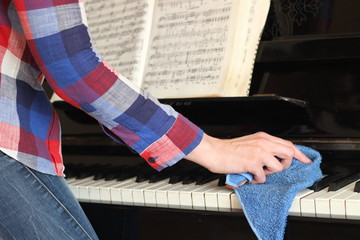 Women's hand with blue cloth to wipe the dust from the piano