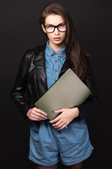 Beautiful young woman in glasses on a black background