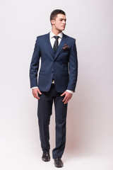 Handsome young businessman  in suit standing against white background