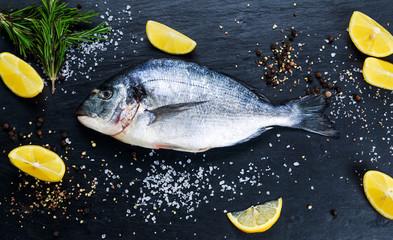 Fresh Raw Sea Bream Fish on blue stone background.