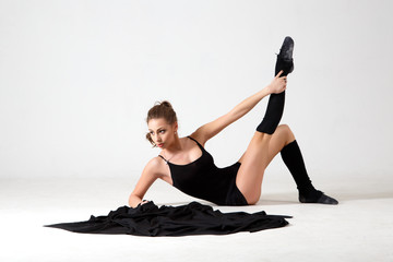 Dancing lady in a black clothes. Contemporary modern dance on a white background isolated. Fitness, stretching model