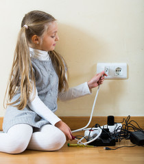 Small girl playing with charging units and smiling