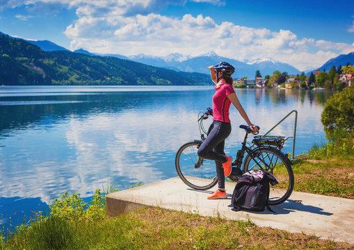 woman with e-bike enjoying view over lake