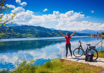 woman with e-bike enjoying view over lake-lake and bike 02