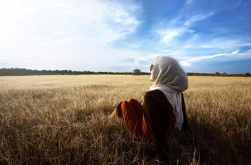 Muslim woman wearing hijab relaxing on savanna