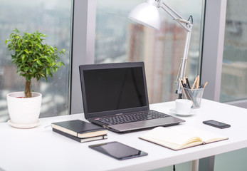 Office workplace with notebook on wood table.
