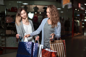 Beautiful girls girlfriends consider their purchases. Fashion Shopping two ladies Portrait. Beauty Woman with Shopping Bags in Shopping Mall. Shopper. Sales. Shopping Center