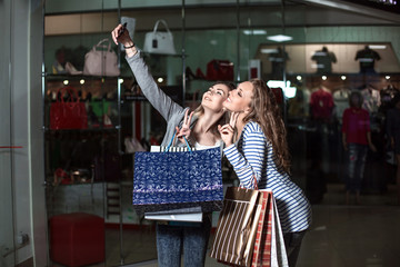 "Beautiful girls with shopping bags taking a ""selfie"" with their cell phone"