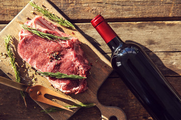 Wall Mural - Raw pork steak with bottle of red wine, meat fork and rosemary on wooden background