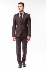 Handsome young businessman  with luck in suit standing against white background