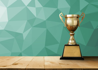 golden trophy on wood table with vintage White Polygonal Mosaic