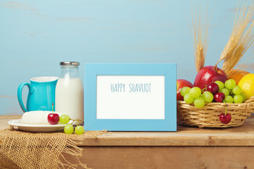 Poster mock up template for Jewish holiday Shavuot. Milk and fruits on wooden table.