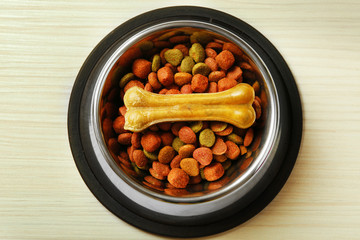 Dog food in metal bowl on wooden background