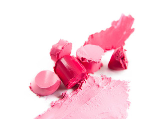 Crushed sliced pink lipstick isolated on white background. Texture of damaged pink colored lipstick on white. Pieces of colorful lipstick closeup.