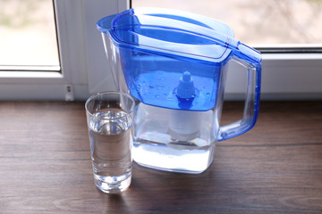 Water filter jug and a glass on the wooden windowsill