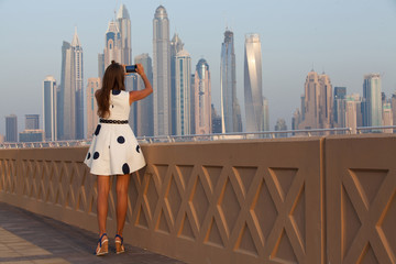Tourist taking travel picture with phone of Dubai City skyline.