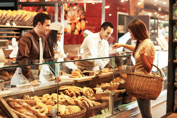 Workers and customer in supermarket bakery