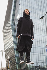 Stylish bearded man levitating in the street