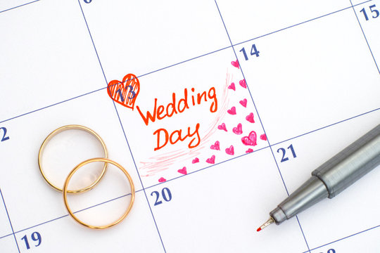 Reminder Wedding day in calendar with pen and two wedding rings