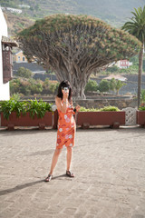 brunette woman with orange dress looking to camera, as photographer taking photo picture, behind The Drago Tree, famous landmark millennial plant, in Icod, Tenerife, Canary Islands, Spain, Europe
