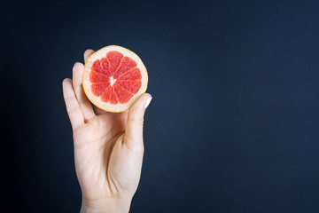 Girls hand holding a halved grapefruit