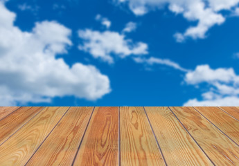 Empty wooden shelves with blue sky and cloud on background. For display product