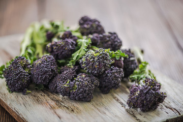 Purple broccoli  on wooden board