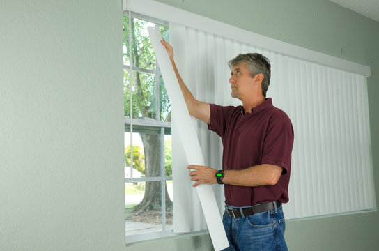 A handy man home repair service technician or home owner hanging white vertical blinds for the window treatment in a new house.