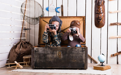 two little girls in hats in big wooden chest playing rarity cameras